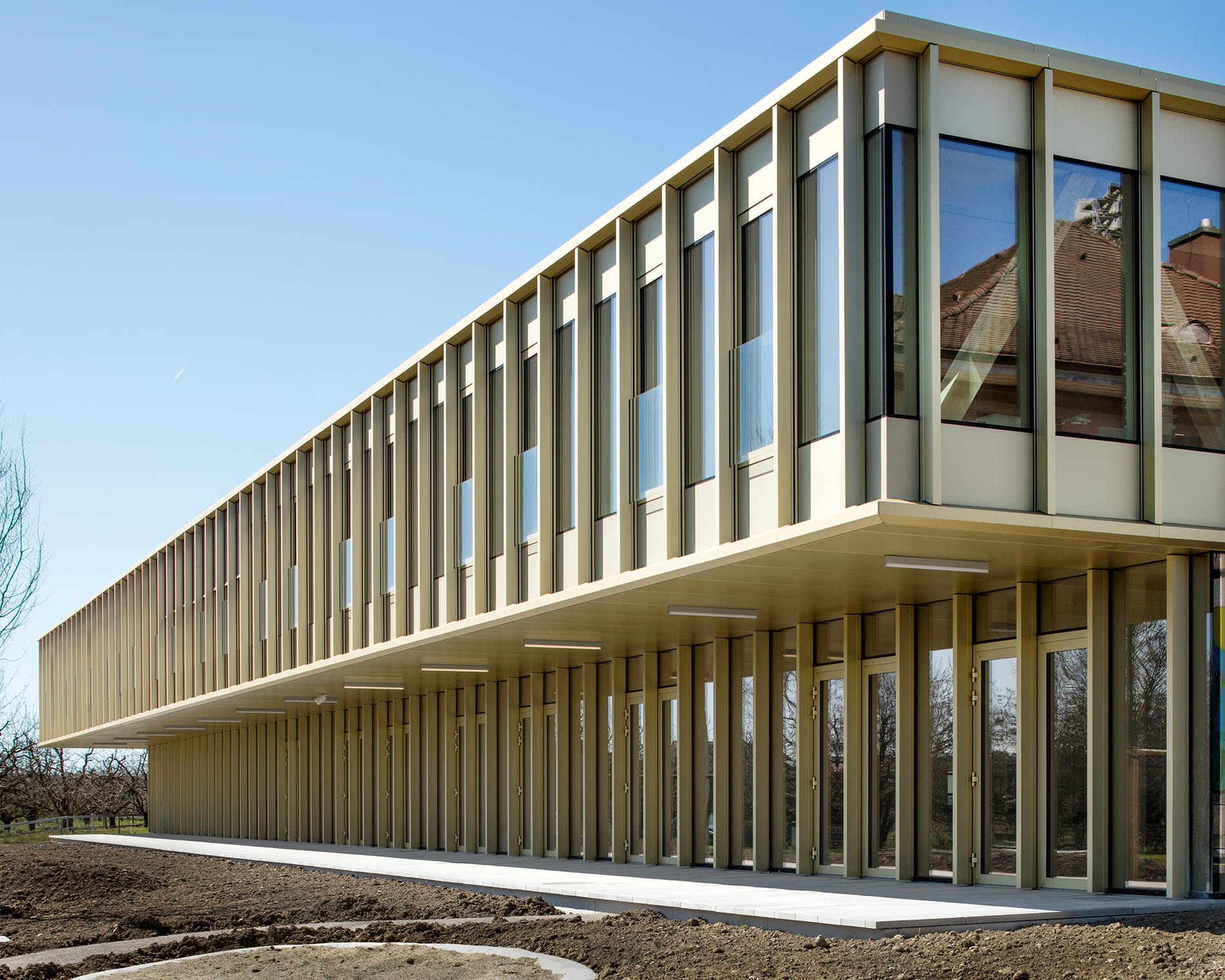 School Building in Sutz-Lattrigen Additional First Floor Cantilevering over the Renovated Ground Floor (© Indermühle Bauingenieure)
